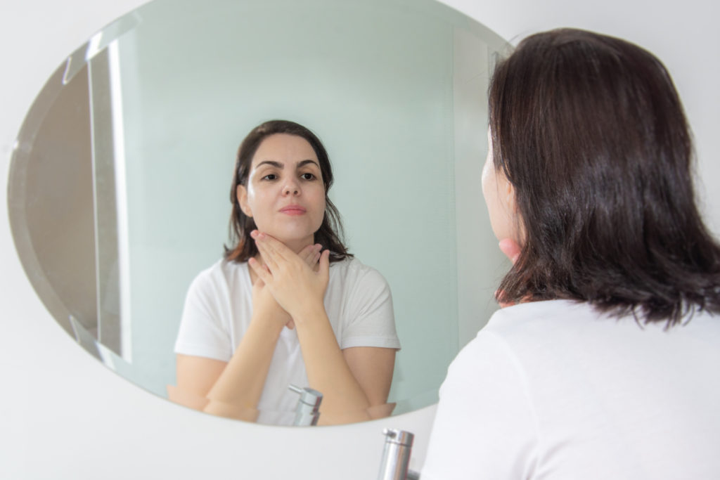 A woman examines her skin type